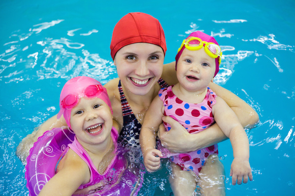 Two little girls in swimming pool with mother, teaching children to swim