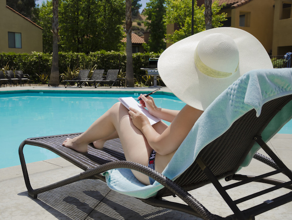 Woman sitting by the pool with a notepad, pool renovations melbourne