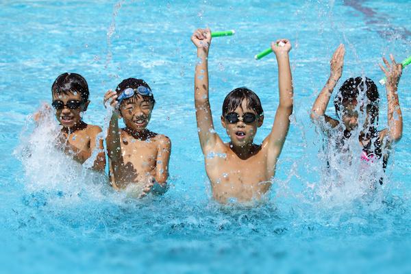 four kids playing swimming pool games