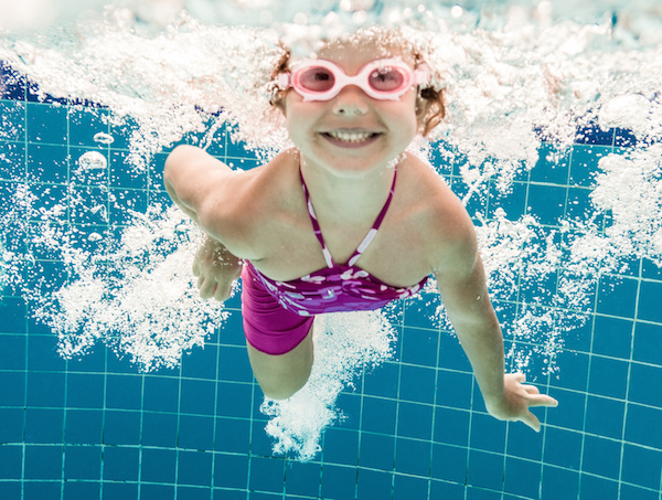 young girl swimming under water in the pool