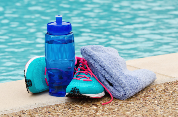 water bottle and running shoes by the pool