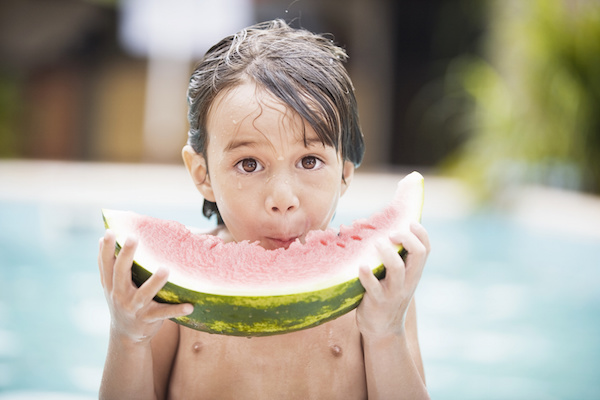 boy eating by the pool