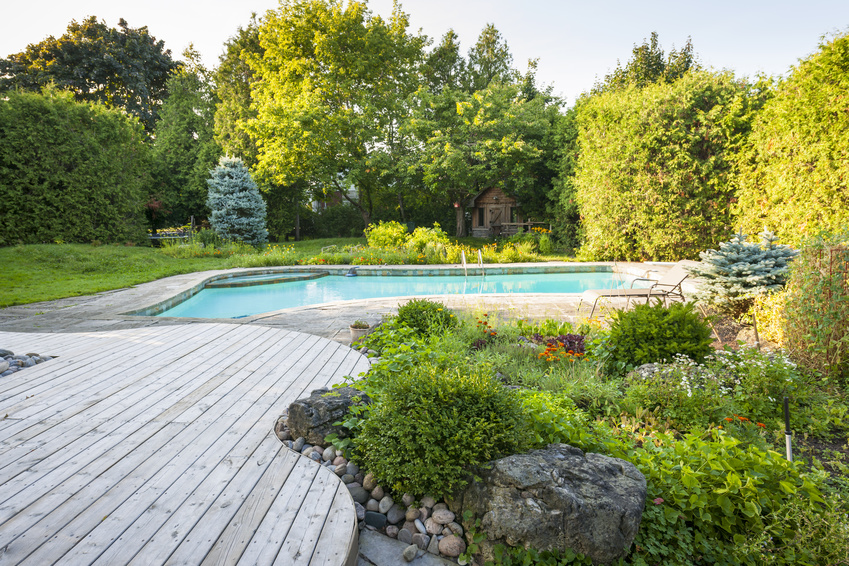 Backyard rock garden with outdoor inground residential swimming pool, curved wooden deck and stone patio